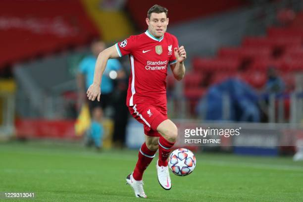Liverpool's English midfielder James Milner runs with the ball during the UEFA Champions league Group D football match between Liverpool and...