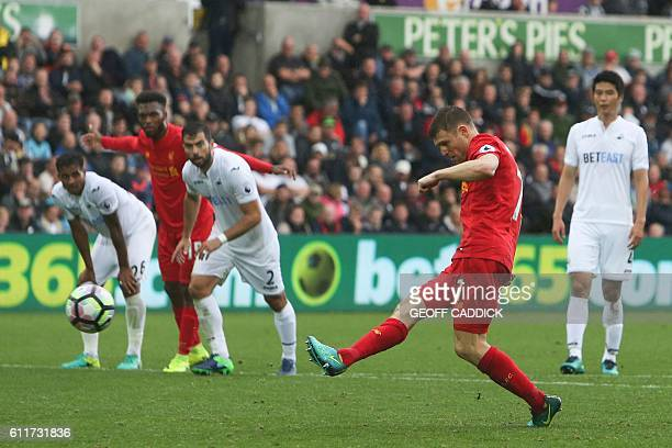 Liverpool's English midfielder James Milner scores their second goal from the penalty spot to take the lead 12 during the English Premier League...