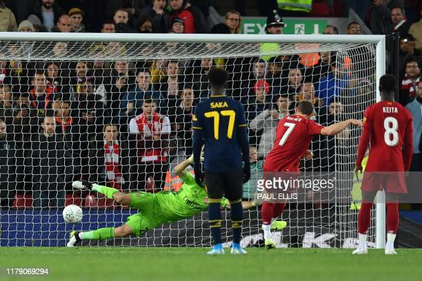 Liverpool's English midfielder James Milner shoots from the penalty spot to score his team's second goal during the English League Cup fourth round...