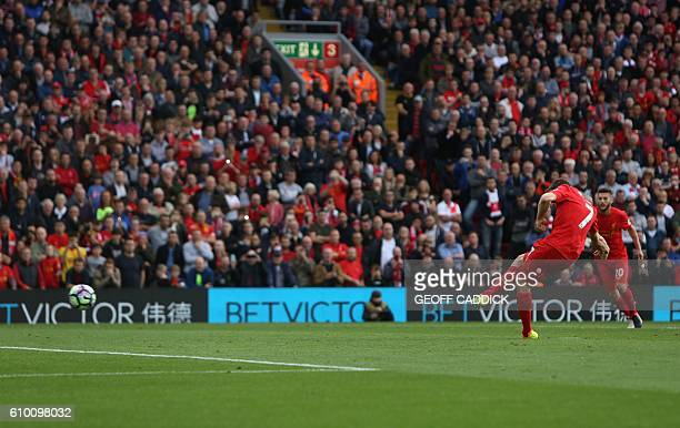 Liverpool's English midfielder James Milner shoots from the penalty spot to score his team's second goal during the English Premier League football...