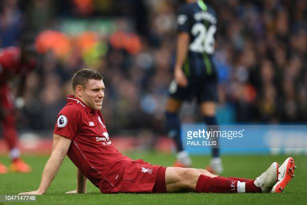 Liverpool's English midfielder James Milner sits on the pitch injured during the English Premier League football match between Liverpool and...