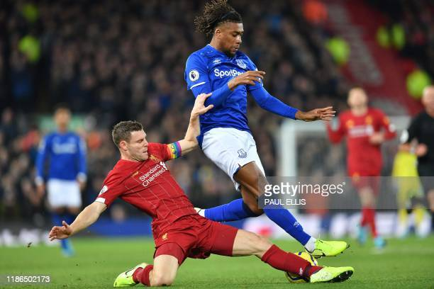 Liverpool's English midfielder James Milner vies with Everton's Nigerian midfielder Alex Iwobi during the English Premier League football match...