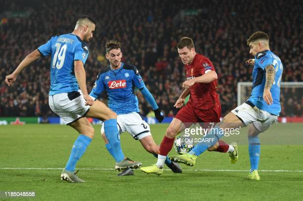 Liverpool's English midfielder James Milner vies with Napoli's Serbian defender Nikola Maksimovic and Napoli's Italian defender Giovanni Di Lorenzo...