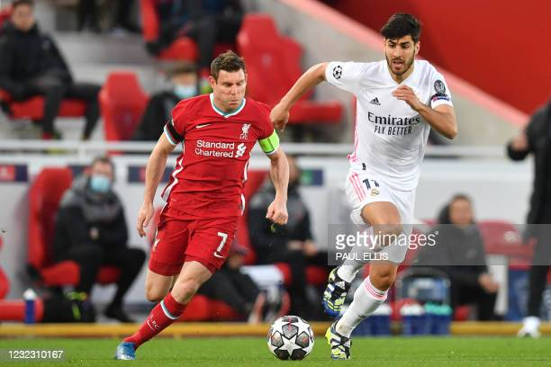 Liverpool's English midfielder James Milner vies with Real Madrid's Spanish midfielder Marco Asensioduring the UEFA Champions League quarter final...