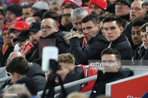 Liverpool's English midfielder James Milner watches from his seat during the English FA Cup fourth round reply football match between Liverpool and...