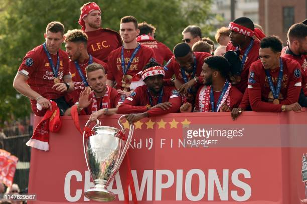 Liverpool's English midfielder Jordan Henderson and Liverpool's Belgian striker Divock Origi hold the European Champion Clubs' Cup trophy during an...