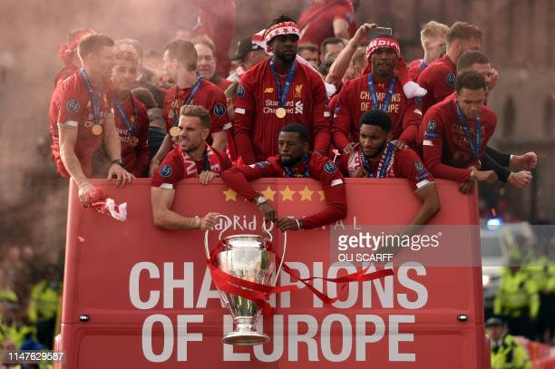 Liverpool's English midfielder Jordan Henderson and Liverpool's Dutch midfielder Georginio Wijnaldum hold the European Champion Clubs' Cup trophy...