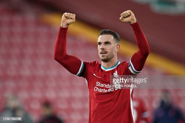 Liverpool's English midfielder Jordan Henderson celebrates after the final whistle during the English Premier League football match between Liverpool...