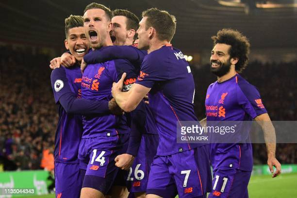 Liverpool's English midfielder Jordan Henderson celebrates with teammates after scoring their third goal during the English Premier League football...