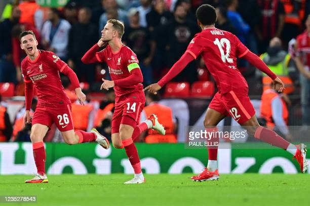 Liverpool's English midfielder Jordan Henderson celebrates with teammates after scoring his team's third goal during the UEFA Champions League 1st...