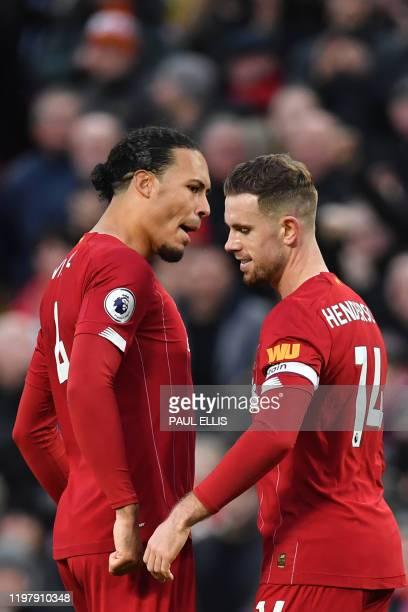 Liverpool's English midfielder Jordan Henderson celebrates with Liverpool's Dutch defender Virgil van Dijk after scoring his team's second goal...