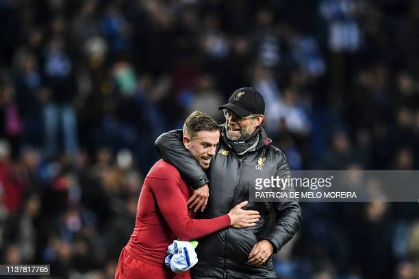 Liverpool's English midfielder Jordan Henderson celebrates with Liverpool's German coach Jurgen Klopp their win at the end of the UEFA Champions...