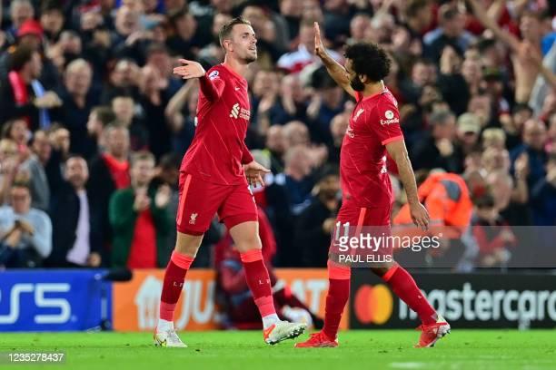 Liverpool's English midfielder Jordan Henderson celebrates with Liverpool's Egyptian midfielder Mohamed Salah after scoring his team's third goal...