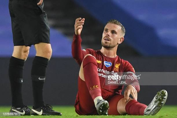 Liverpool's English midfielder Jordan Henderson goes down after tacking knock during the English Premier League football match between Brighton and...