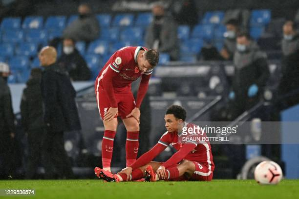 Liverpool's English midfielder Jordan Henderson leans over teammate Trent Alexander-Arnold as he sits on the ground after picking up an injury during...