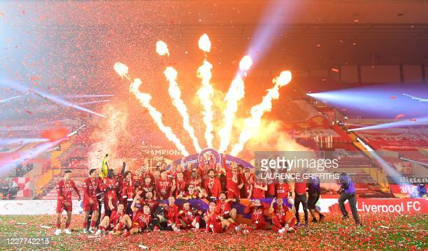Liverpool's English midfielder Jordan Henderson lifts the Premier League trophy in the middle of his team-mates during the presentation following the...