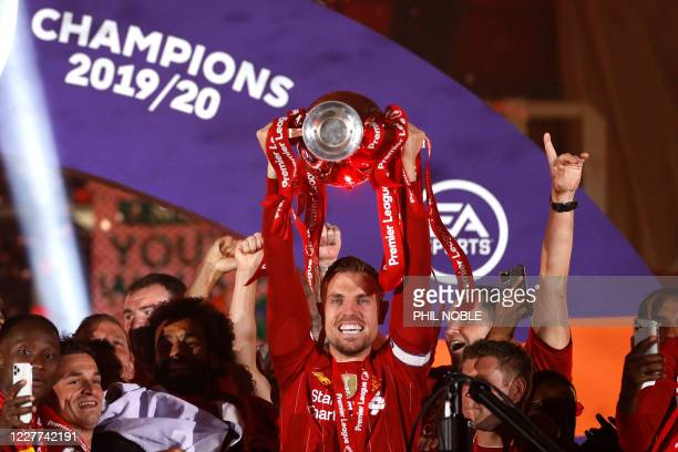 Liverpool's English midfielder Jordan Henderson lifts the Premier League trophy with his team-mates during the presentation following the English...