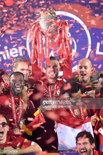 Liverpool's English midfielder Jordan Henderson lifts the Premier League trophy during the presentation following the English Premier League football...