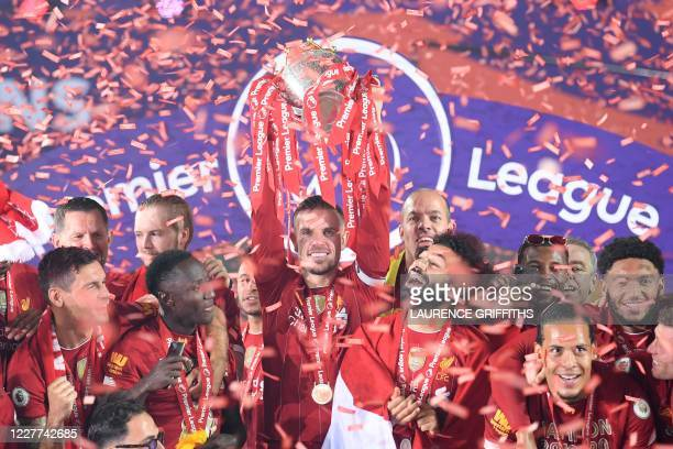 Liverpool's English midfielder Jordan Henderson lifts the Premier League trophy during the presentation following the English Premier League football...