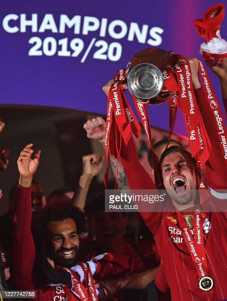 Liverpool's English midfielder Jordan Henderson lifts the Premier League trophy with Liverpool's Egyptian midfielder Mohamed Salah during the...