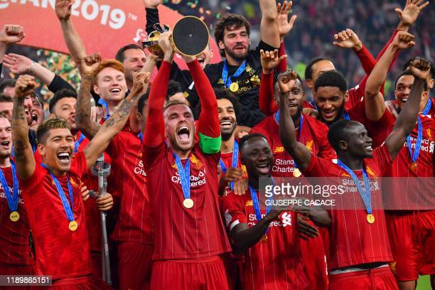 Liverpool's English midfielder Jordan Henderson lifts the trophy after winning the 2019 FIFA Club World Cup Final football match between England's...