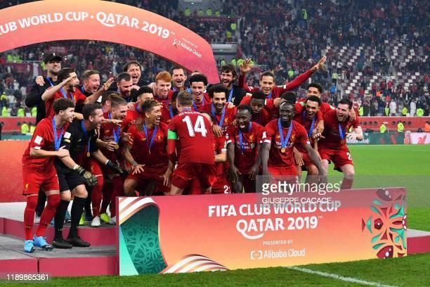 Liverpool's English midfielder Jordan Henderson lifts the trophy after winning the 2019 FIFA Club World Cup Final football match between England's...