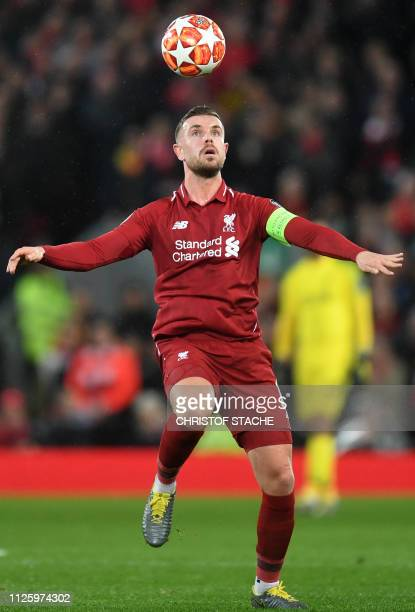 Liverpool's English midfielder Jordan Henderson plays the ball during the UEFA Champions League round of 16 first leg football match between...