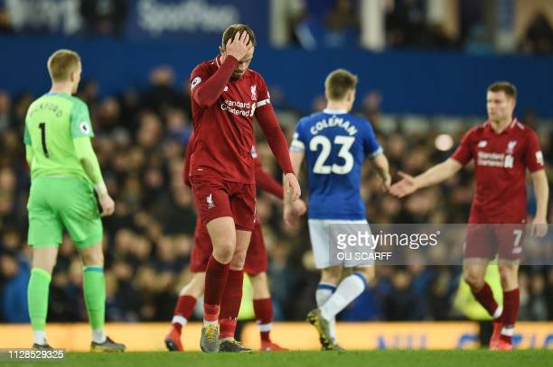 Liverpool's English midfielder Jordan Henderson reacts after drawing the English Premier League football match between Everton and Liverpool at...