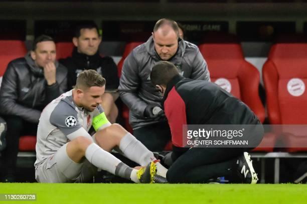 Liverpool's English midfielder Jordan Henderson recieves medical attention during the UEFA Champions League last 16 second leg football match Bayern...