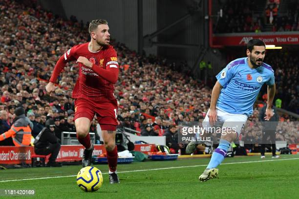 Liverpool's English midfielder Jordan Henderson runs with the ball in the buildup to their third goal during the English Premier League football...