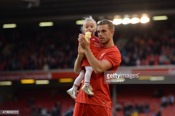 Liverpool's English midfielder Jordan Henderson salutes the fans with his daughter Elexa at the end of the English Premier League football match...