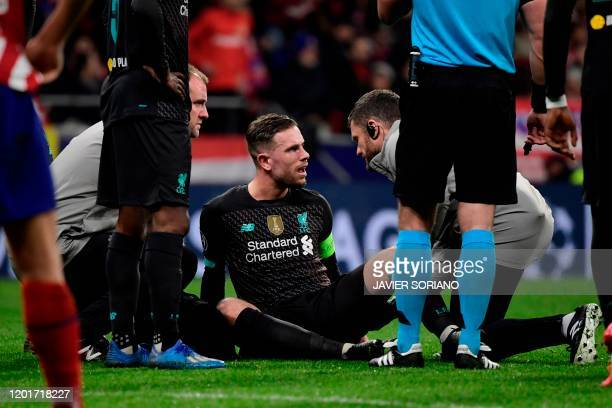Liverpool's English midfielder Jordan Henderson sits on the field during the UEFA Champions League, round of 16, first leg football match between...