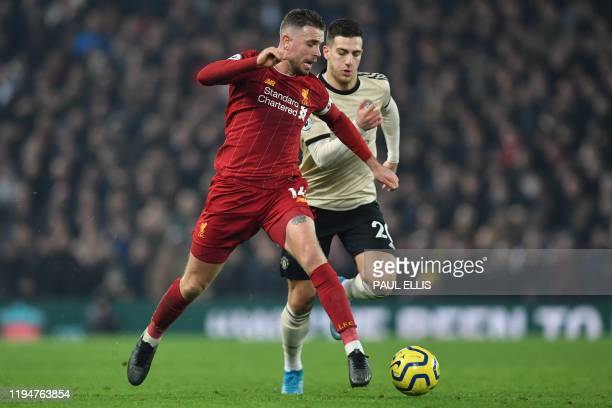 Liverpool's English midfielder Jordan Henderson takes on Manchester United's Portuguese defender Diogo Dalot during the English Premier League...