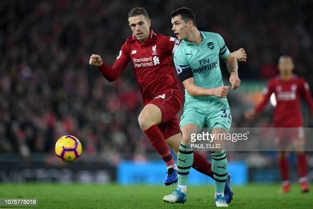 Liverpool's English midfielder Jordan Henderson vies with Arsenal's Swiss midfielder Granit Xhaka during the English Premier League football match...