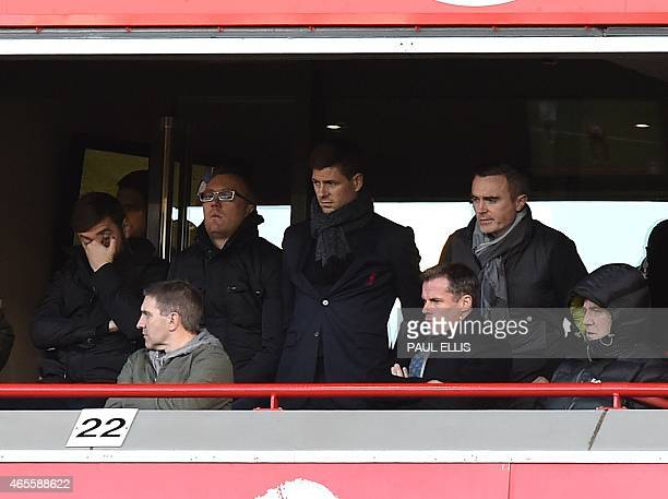 Liverpool's English midfielder Steven Gerrard and former player television pundit Jamie Carragher watch from a box during the FA Cup quarterfinal...