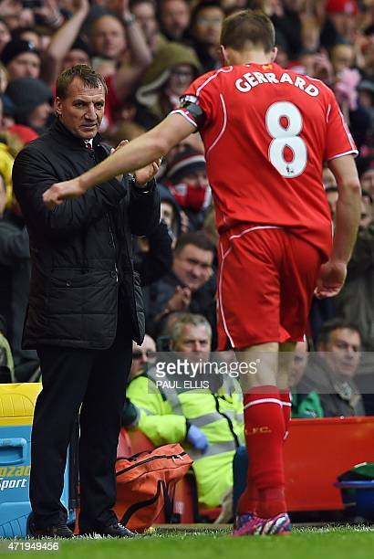 Liverpool's English midfielder Steven Gerrard is applauded by Liverpool's Northern Irish manager Brendan Rodgers as he is substituted after scoring...