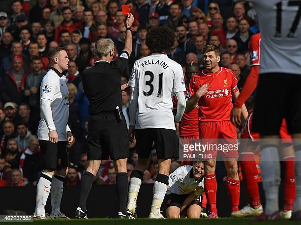Liverpool's English midfielder Steven Gerrard is shown a red card by referee Martin Atkinson in the first minute of the second half, after coming on...