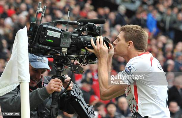 Liverpool's English midfielder Steven Gerrard kisses a television camera after scoring his team's second goal during the English Premier League...