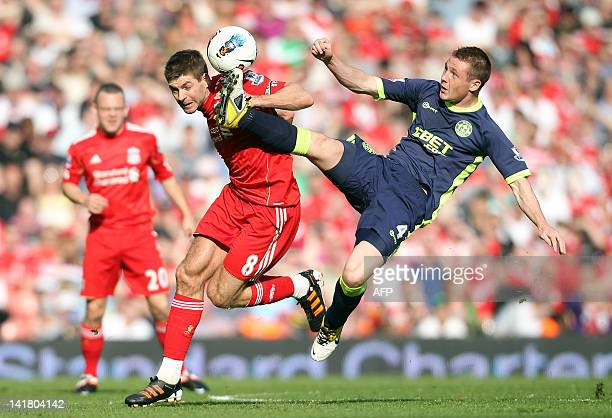 Liverpool's English midfielder Steven Gerrard vies with Wigan Athletic's Scottish defender James McCarthy during the English Premier League football...