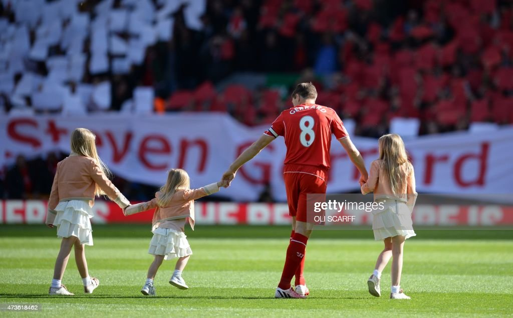 Liverpool's English midfielder Steven Gerrard (2R) walks onto the pitch with his daughters Lilly-Ella, Lourdes and Lexie at the start of the English Premier League football match between Liverpool and Crystal Palace at the Anfield stadium in Liverpool, northwest England, on May 16, 2015. AFP PHOTO / OLI SCARFF USE. No use with unauthorized audio, video, data, fixture lists, club/league logos or live services. Online in-match use limited to 45 images, no video emulation. No use in betting, games or single club/league/player publications. /