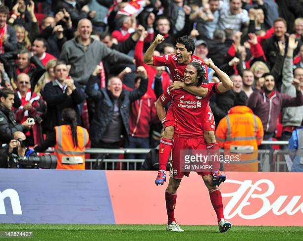 Liverpool's English striker Andy Carroll celebrates with teammate Luis Suarez after scoring the winning goal of the FA Cup semifinal football match...
