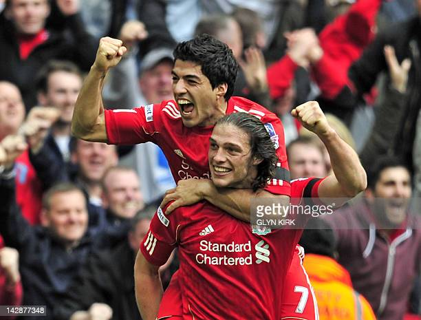 Liverpool's English striker Andy Carroll celebrates with team-mate Luis Suarez after scoring the winning goal of the FA Cup semi-final football match...