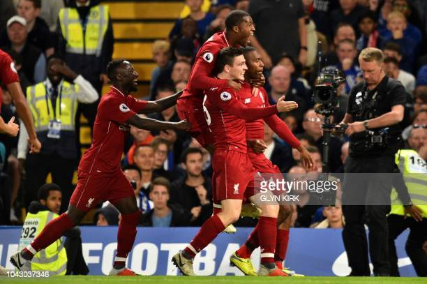 Liverpool's English striker Daniel Sturridge celebrates with teammates after scoring the team's first goal during the English Premier League football...