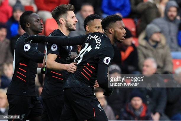 Liverpool's English striker Daniel Sturridge celebrates with teammates after scoring the opening goal of the English Premier League football match...
