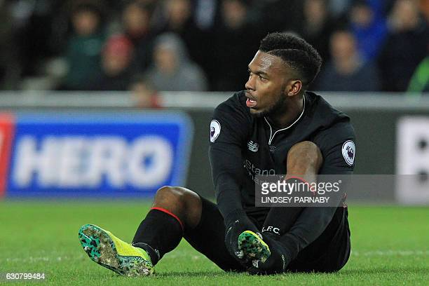 Liverpool's English striker Daniel Sturridge holds his foot after appearing to pick up an injury during the English Premier League football match...
