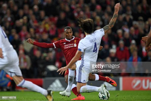 Liverpool's English striker Daniel Sturridge shoots to score their third goal during the UEFA Champions League Group E football match between...