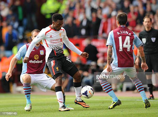 Liverpool's English striker Daniel Sturridge vies with Aston Villa's Dutch defender Ron Vlaar and Spanish defender Antonio Luna during the English...