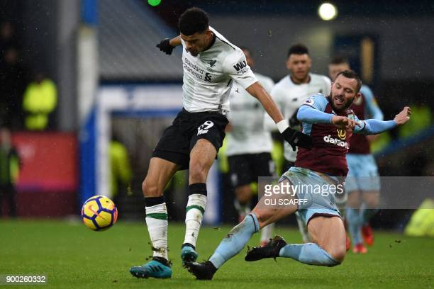 Liverpool's English striker Dominic Solanke is tackled by Burnley's Englishborn Scottish defender Phil Bardsley during the English Premier League...