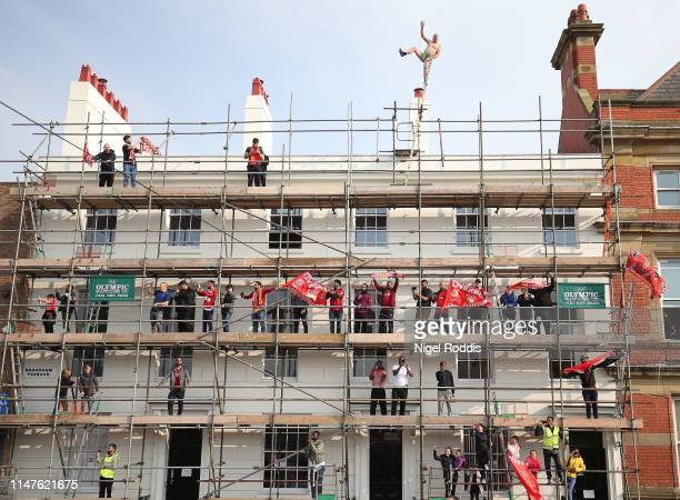 Liverpool's fans stand on scaffolding to watch the UEFA Champions League victory parade after Liverpool won yesterday's final against Tottenham...