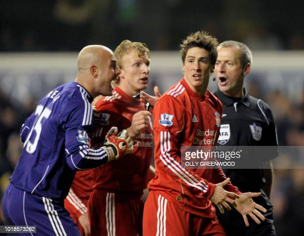 Liverpool's Fernando Torres and Pepe Reina and Dirk Kuyt argue with referee Martin Atkinson after he awarded a penalty to Tottenham Hotspur during...